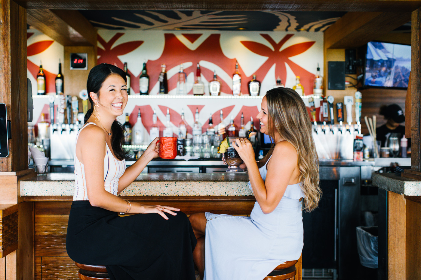 Two women enjoying drinks at the bar