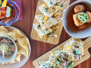 Multiple plated dishes with tacos, quesadilla,drinks